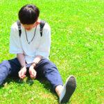 芝生に座っている男性