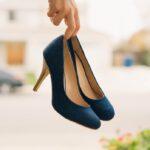 手にヒール靴を持っている女性の指先