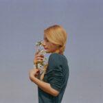 横を向いて花を持っている金髪の女性