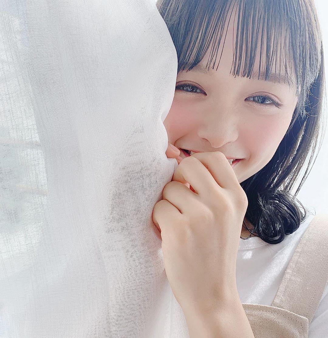 カーテンの袖から顔を出している女性