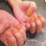 オレンジ色のネイルをしている女性の両手