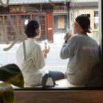 カフェの軒先に座る女性と男性