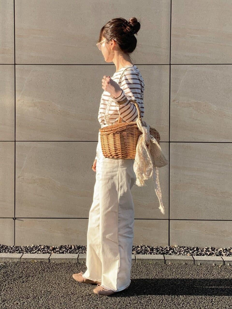 バッグを手に抱え、横向きの女性の全身写真