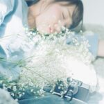 横たわっている女性とその前にある花束