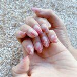 両手のアップ、ピンク色のネイルを見せているところ