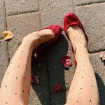 赤い靴とドットタイツを履いた女性の足元