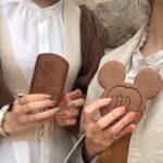 ミッキーマウスのクッキーを持つ女性の手