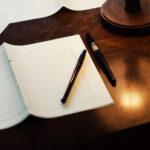 ノートとペンが机の上に置かれている