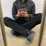 男性が足を組んで座っているところをスマートフォンで撮影している