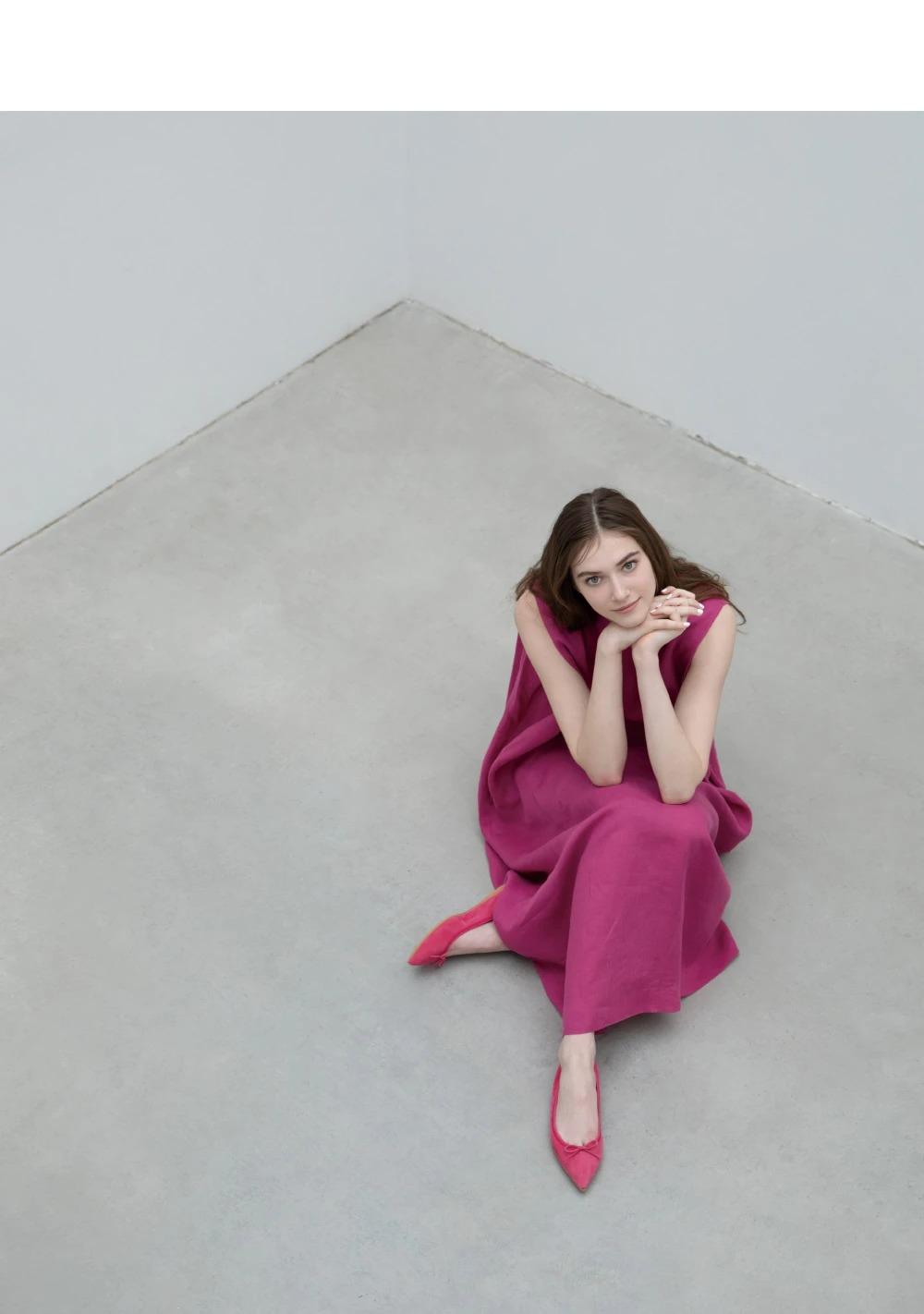 ピンク色のワンピと靴で座っている女性