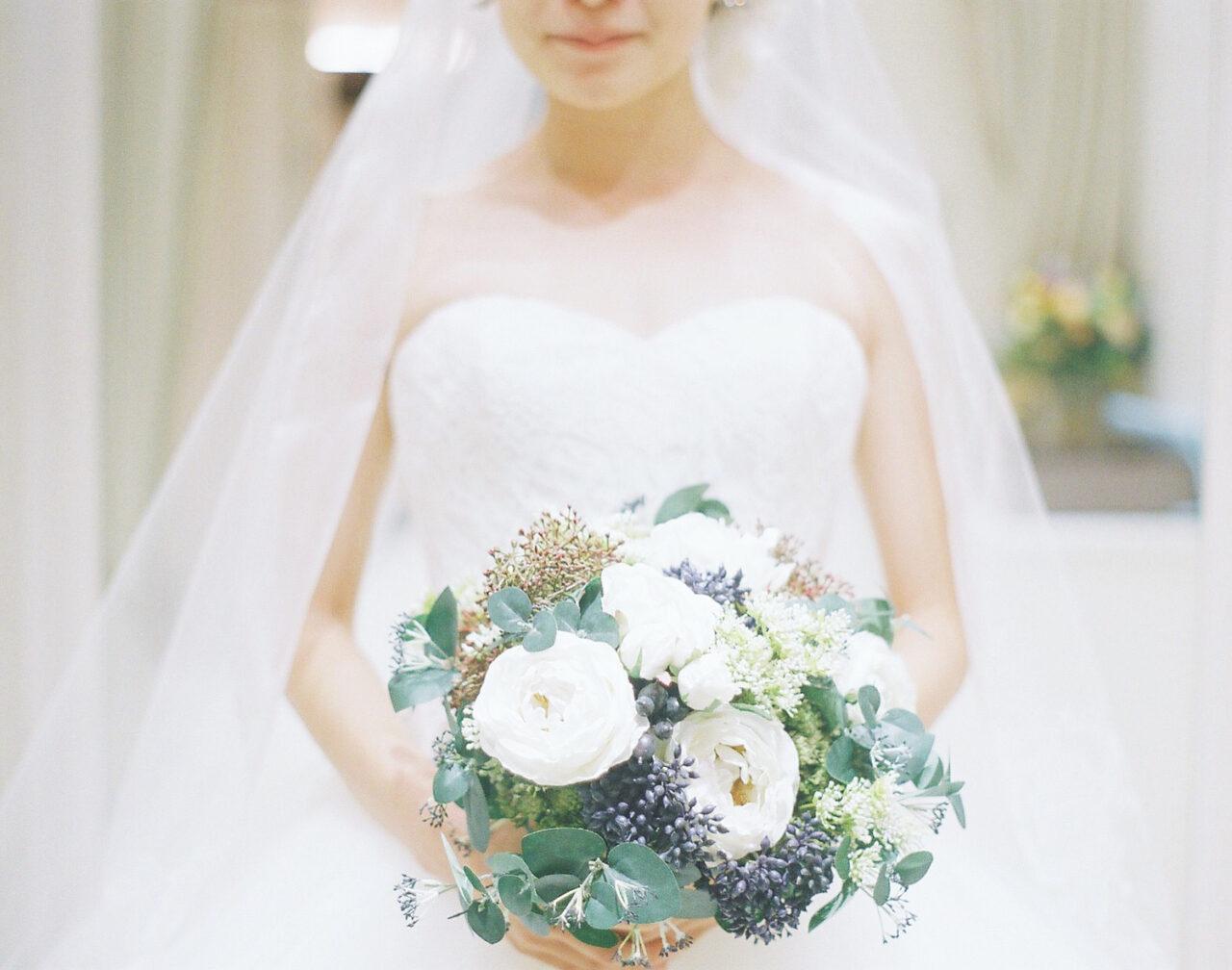 ウエディングドレス姿の花嫁、手にはブーケ