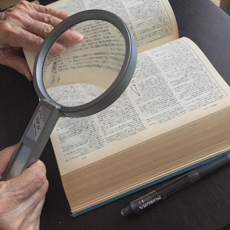 広辞苑を虫眼鏡で見るお年寄り