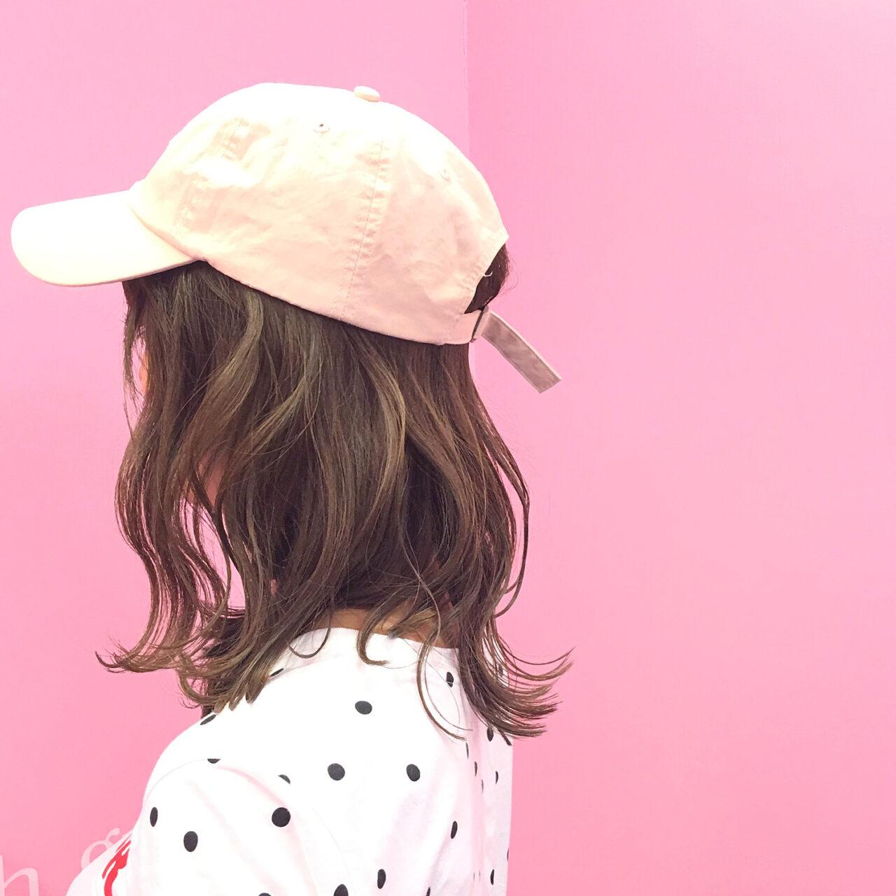 帽子をかぶっているミディアムヘアの女性の横顔