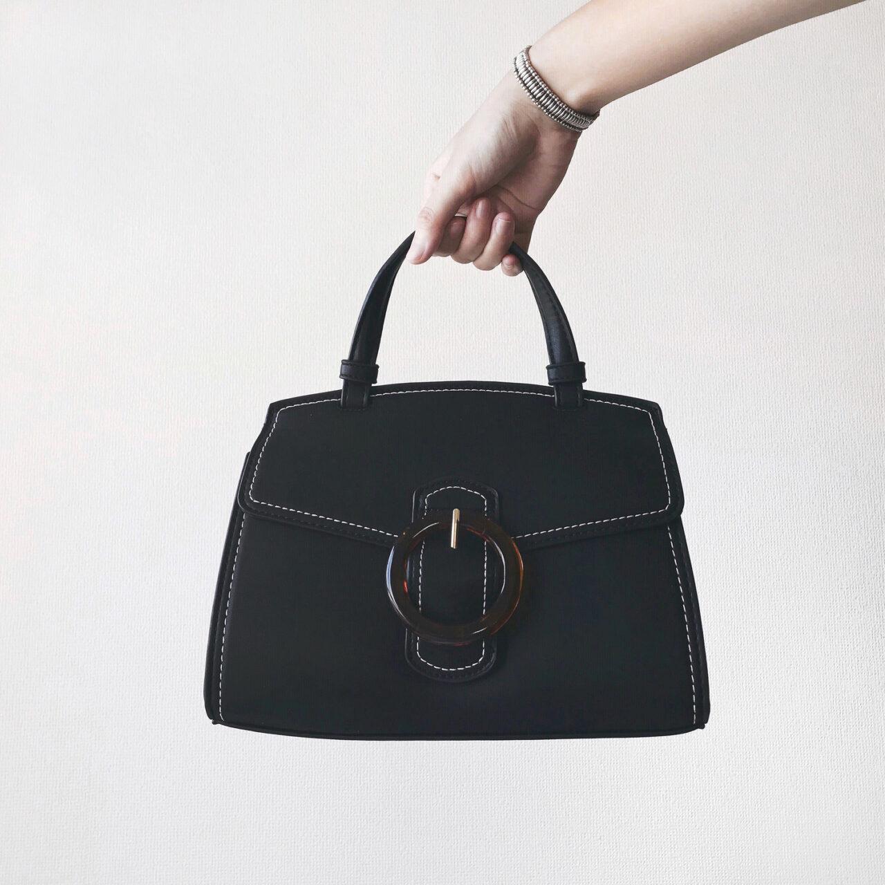 黒いバッグと、それを持つ手袋をした女性の手