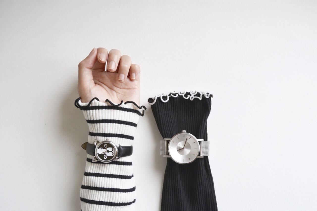 女性の手と、ニットの裾が並んでいるところ。両方とも時計をはめている