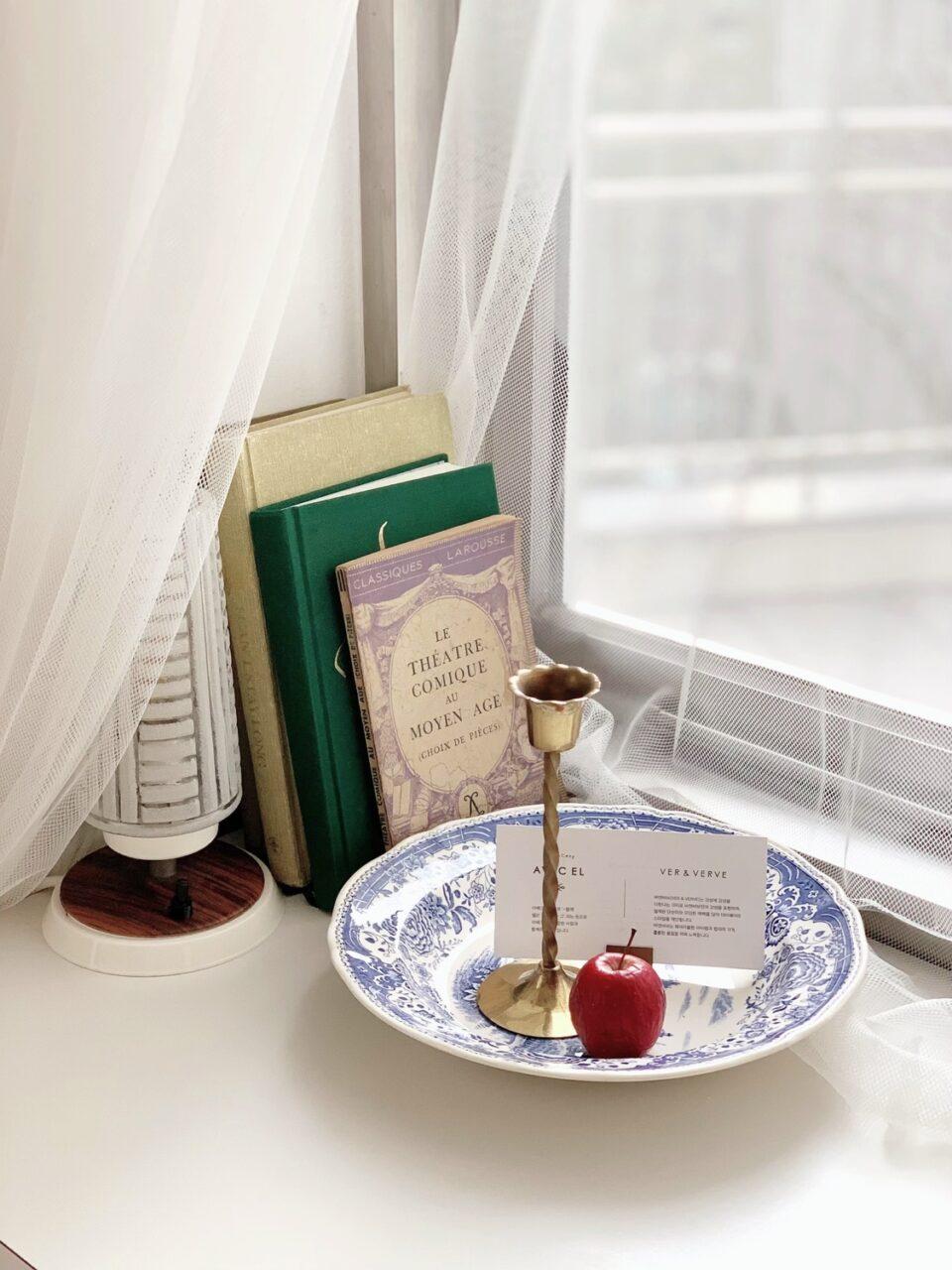 窓際に本が複数立てかけられ、手前にお皿が1枚ある