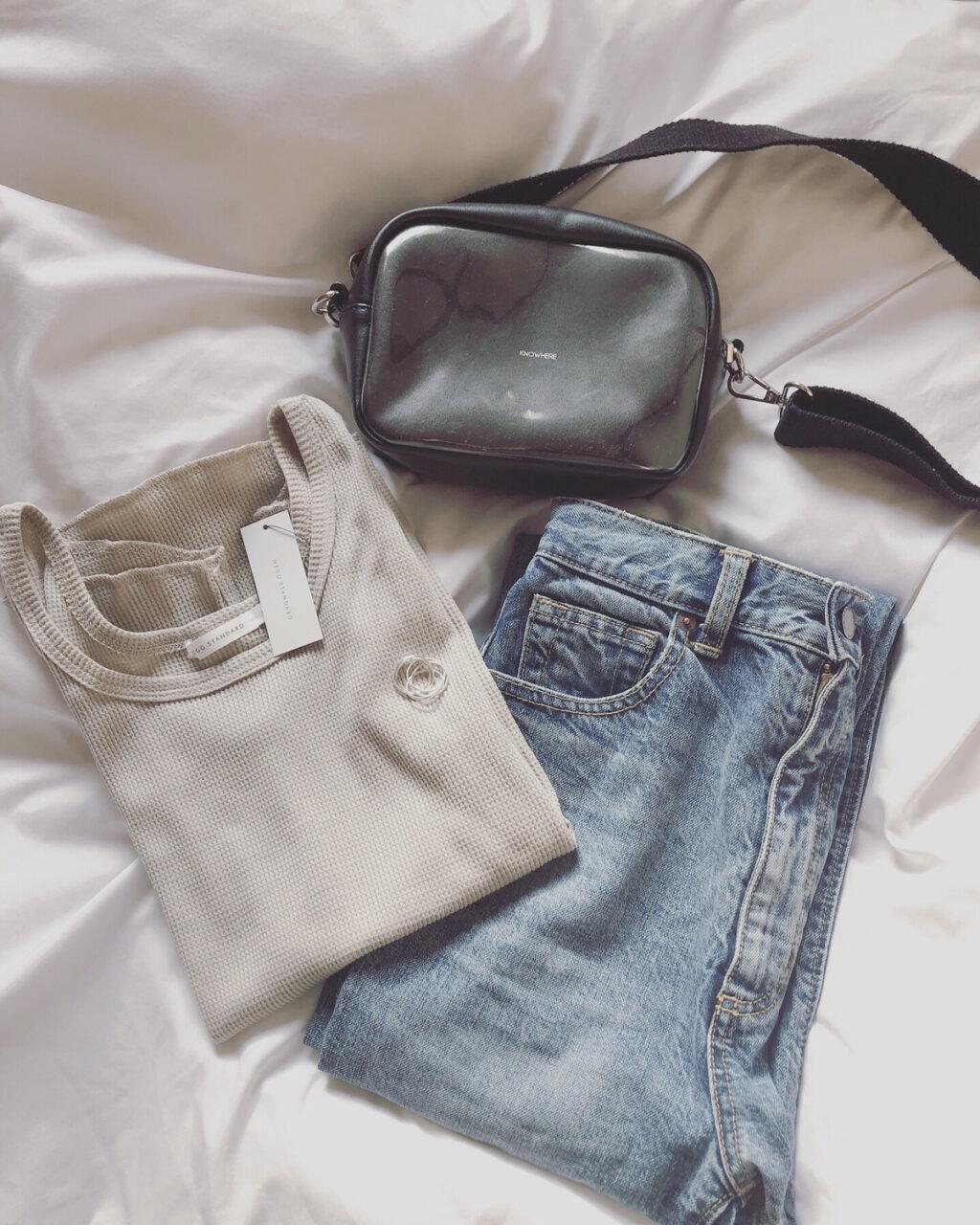 Tシャツ、バッグ、デニムがたたまれてベッドの上に置かれている