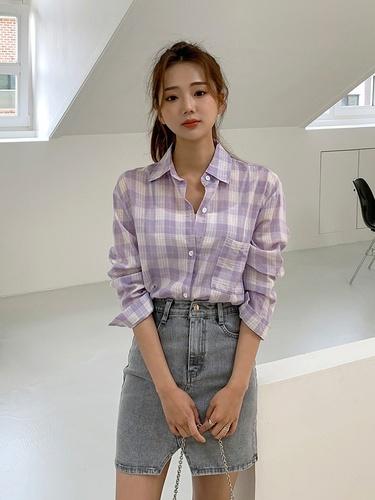 パステルカラー透けチェックシャツとデニムスカートを着こなす女性