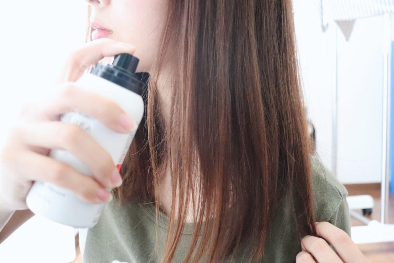 長い髪にスプレーをする女性の横顔