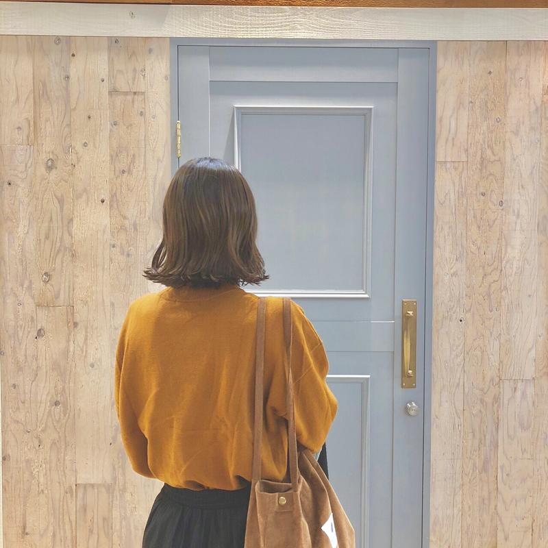 扉の前に立つ女性の後ろ姿