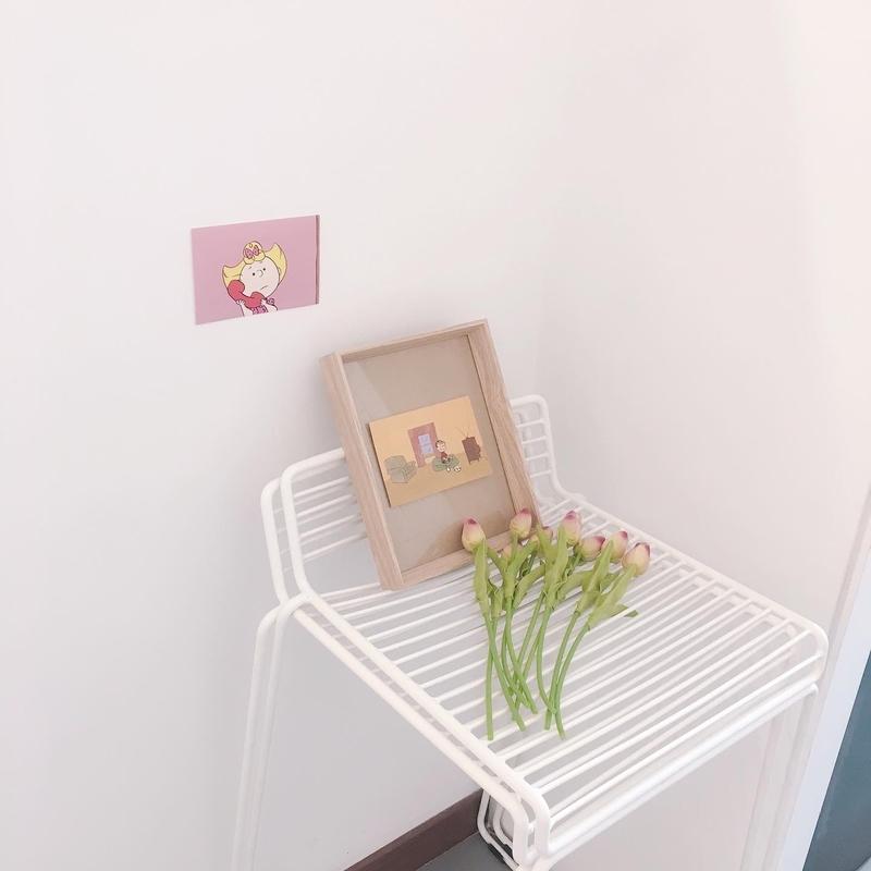 部屋の片隅に椅子が置かれ、その上に花や本が置かれている