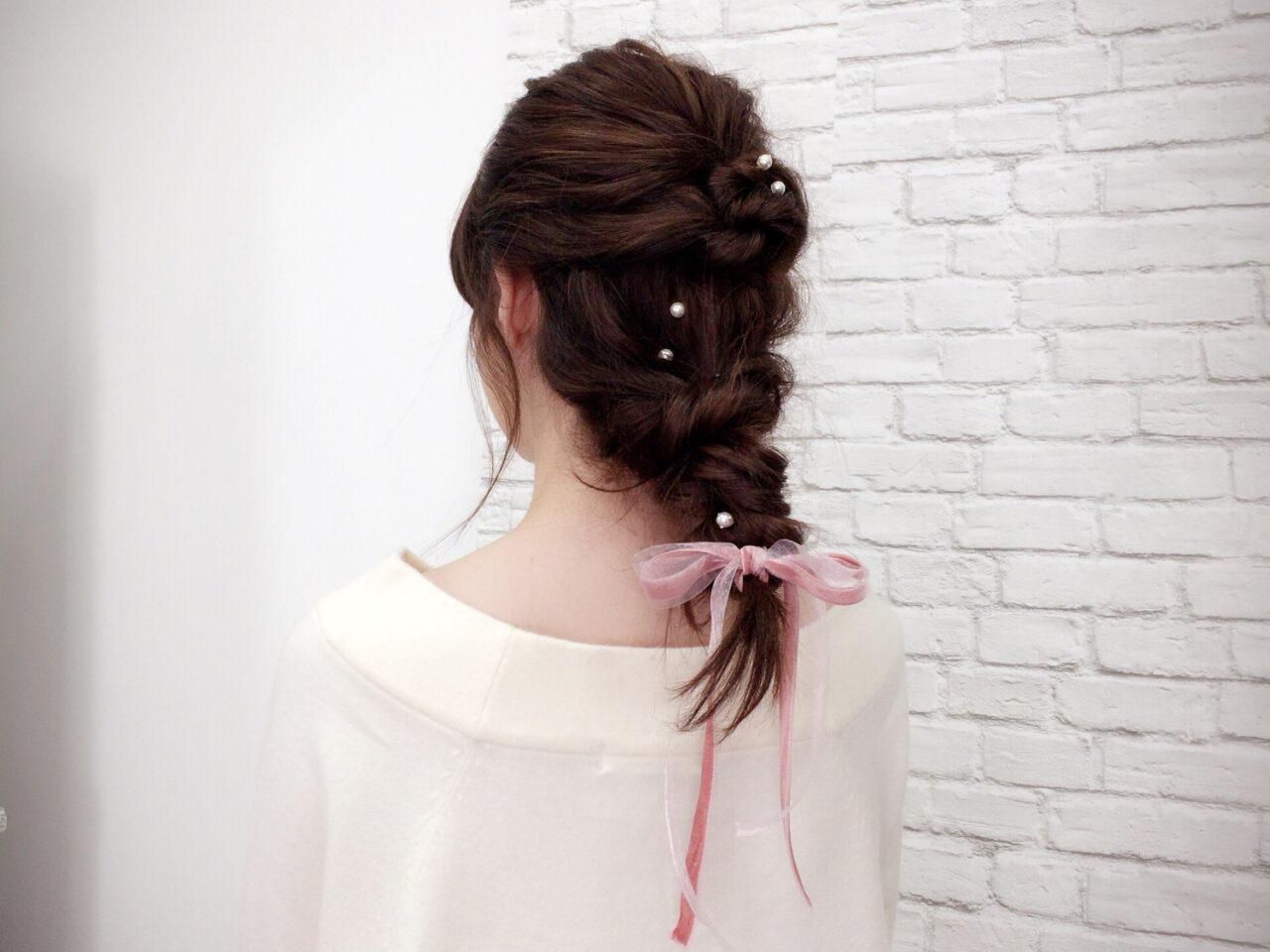 女性の後ろ姿、髪の毛を三つ編みにしリボンで先端を結んでいる
