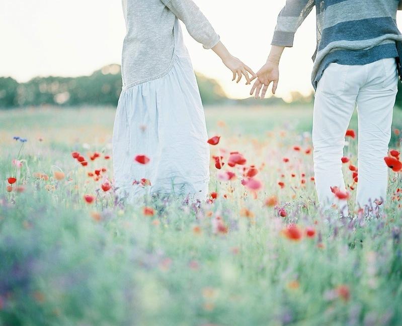 花畑の中、今にも手を繋ぎそうなカップル