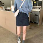 開襟サマーニットカーディガンとデニムスカートを着こなす女性