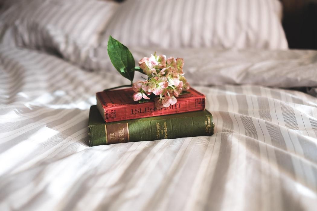 ベッドに置かれた本と花