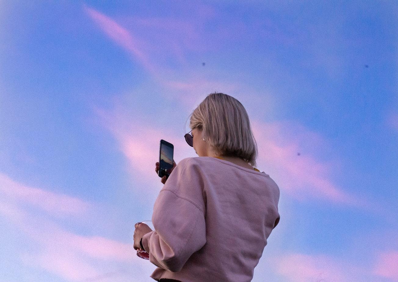 ピンクの空をバックにスマホを見る女性