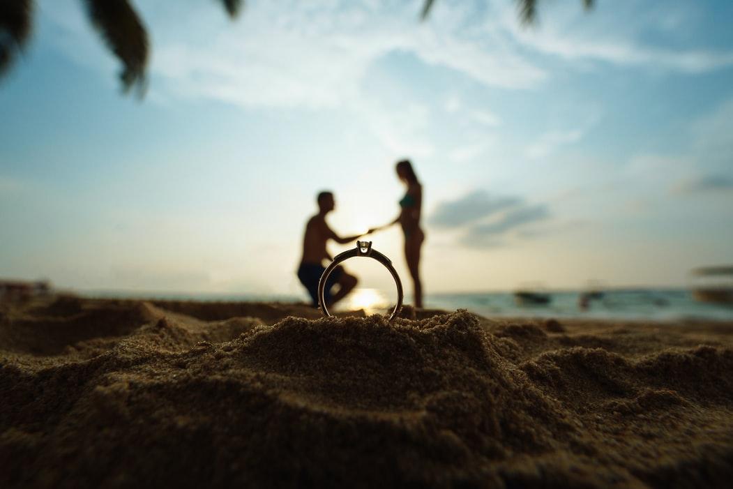海辺でプロポーズ中のカップル
