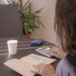 部屋で計算機を片手にノートをつけている女性