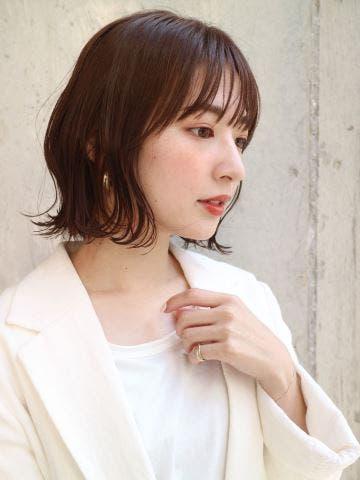 白いジャケットを羽織る女性の横顔