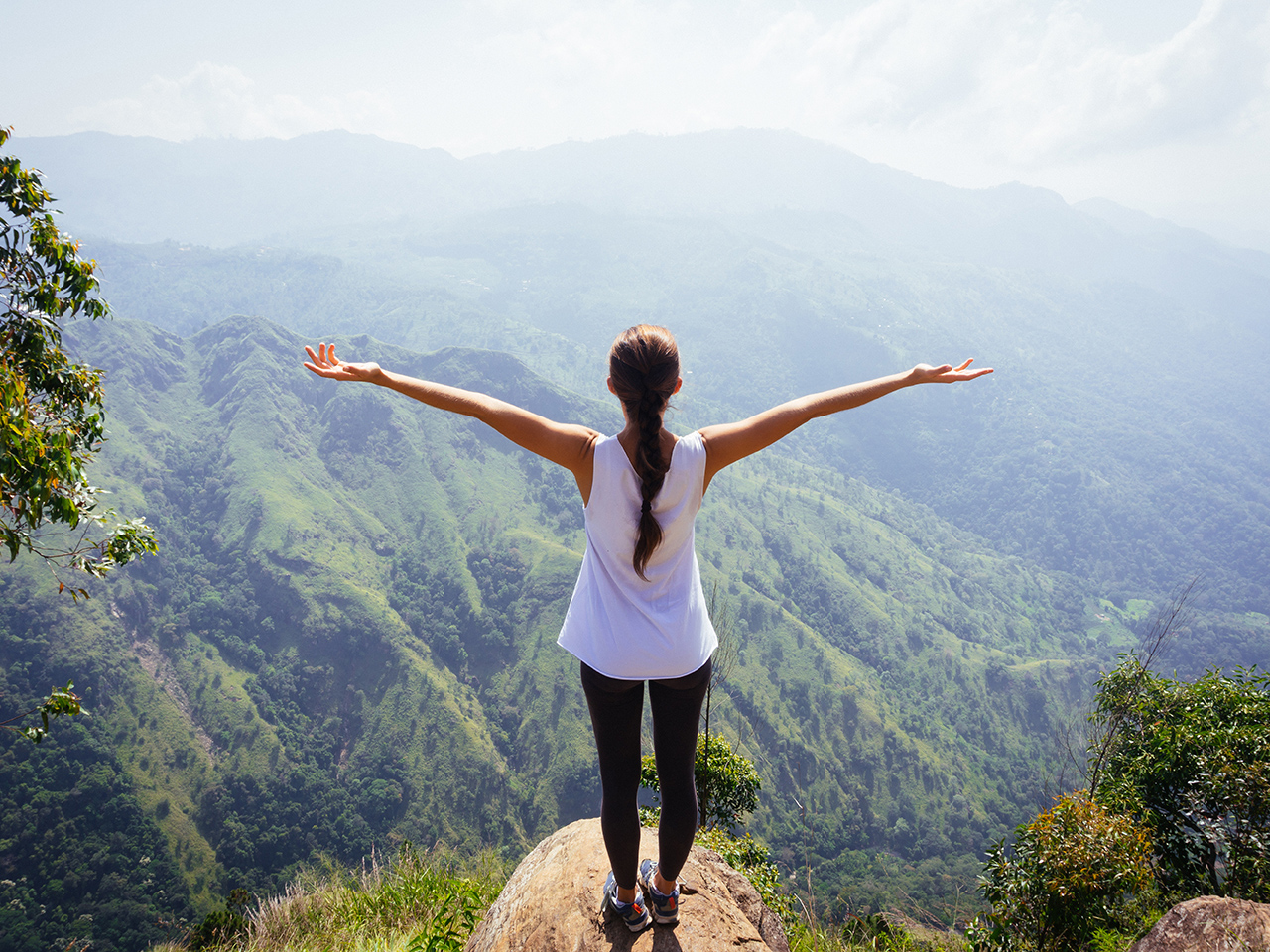 Sporty woman standing with raised arms on the top oh hill