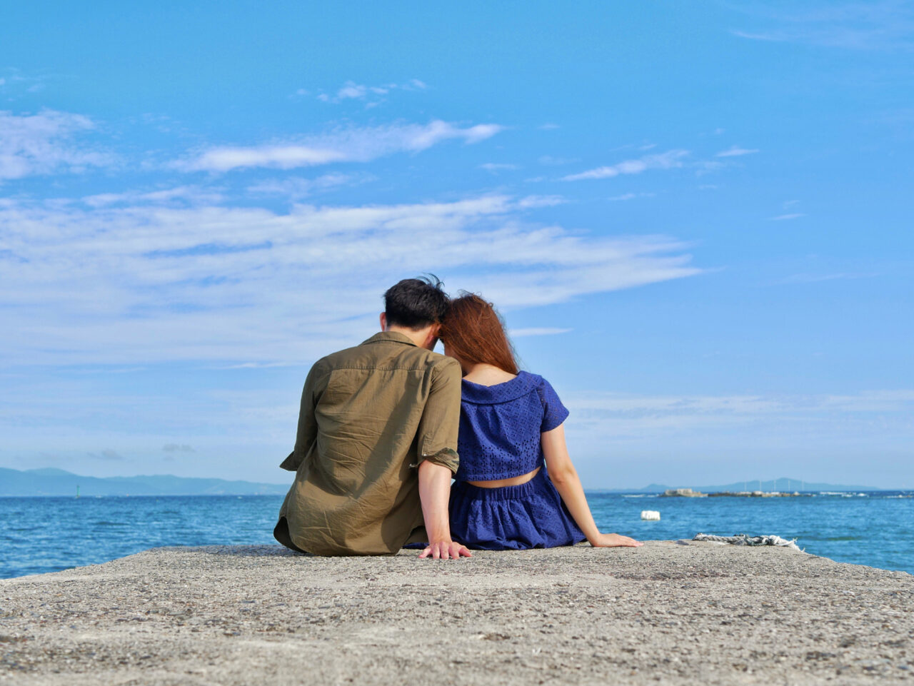海辺でたそがれるカップル