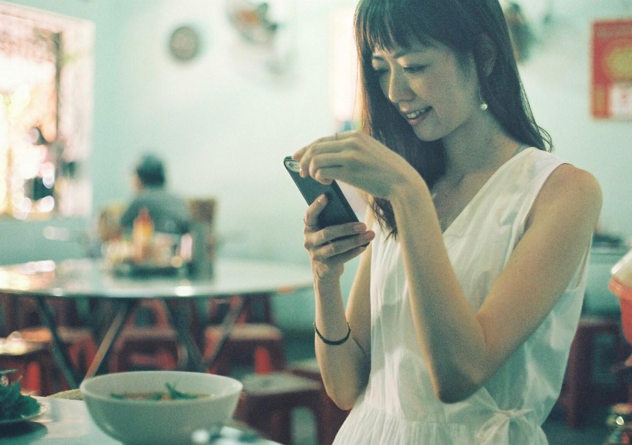 外食しながらスマホを見ている女性