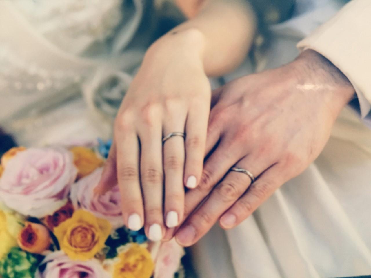 結婚した男女の指輪をつけた手先