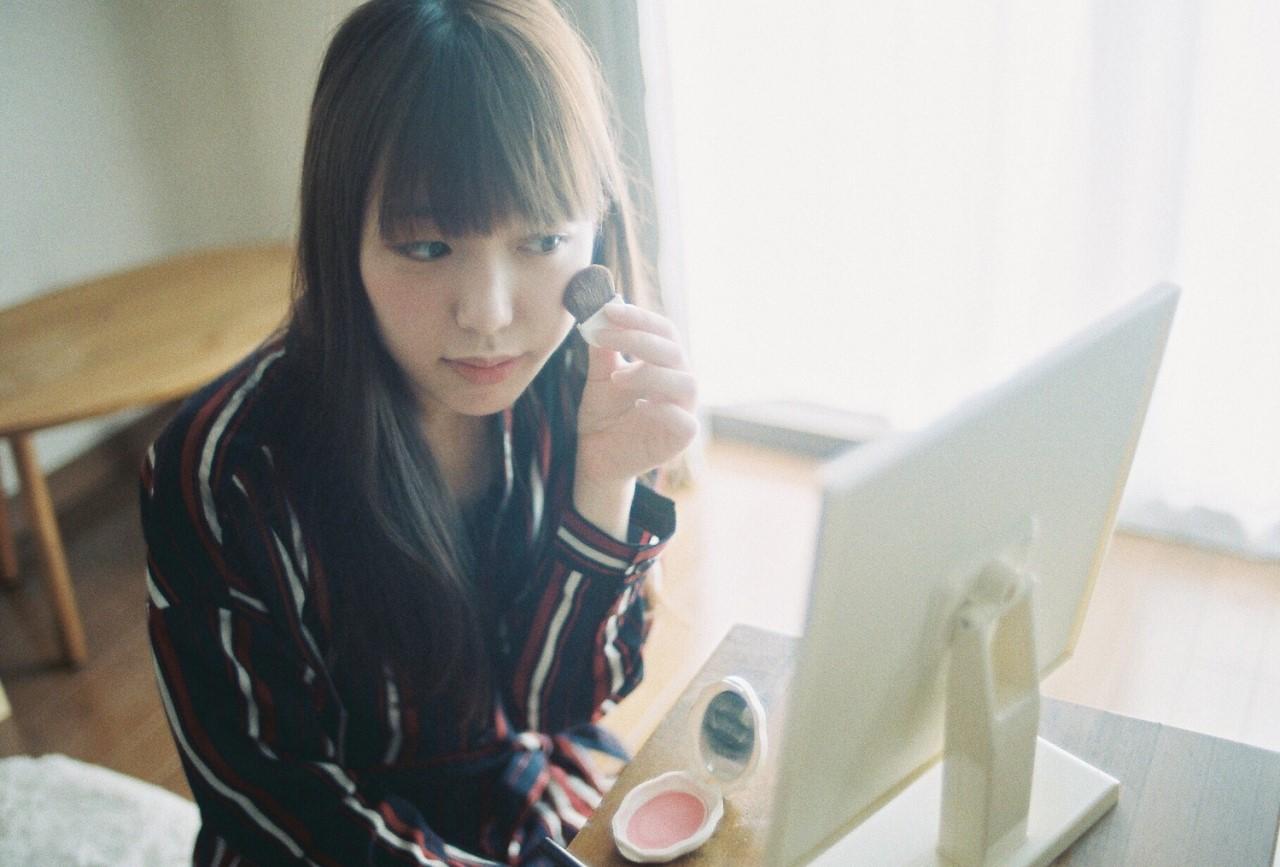 鏡の前でメイクをしている女性