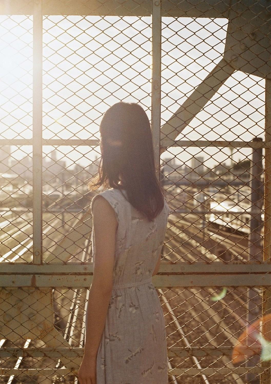 フェンスの向こう側を見つめる女性