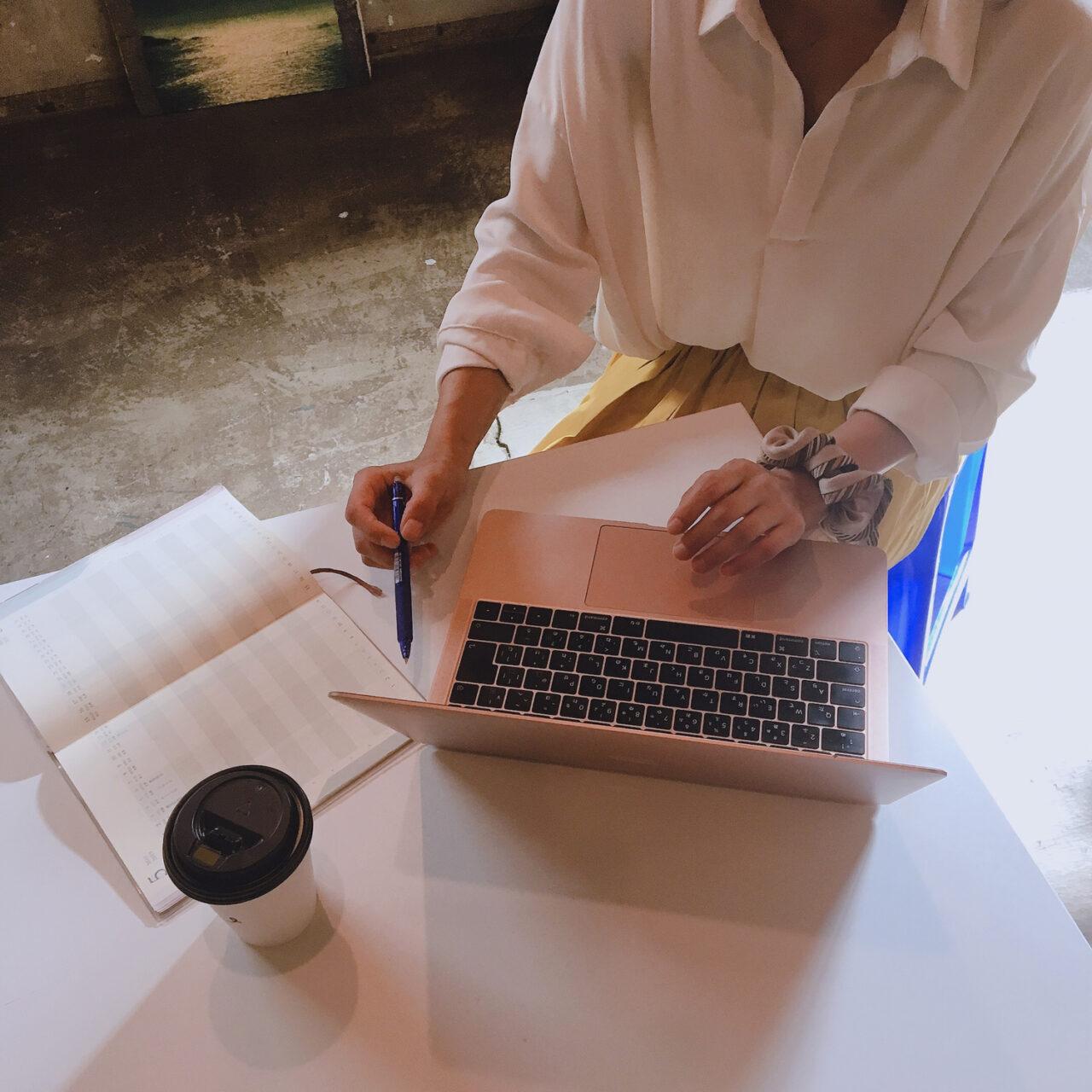 パソコンとノートを見ている女性