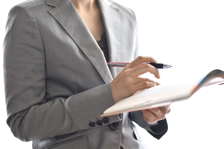 ノートとペンを持っているスーツの女性