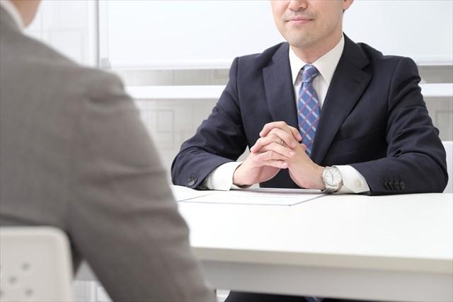 テーブルの上で手を組む男性面接官