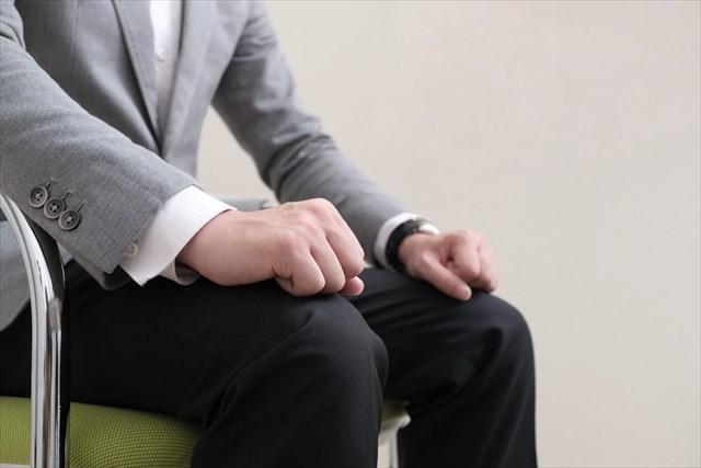 椅子に座っているスーツの男性