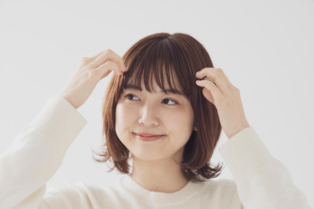 前髪を触る女性