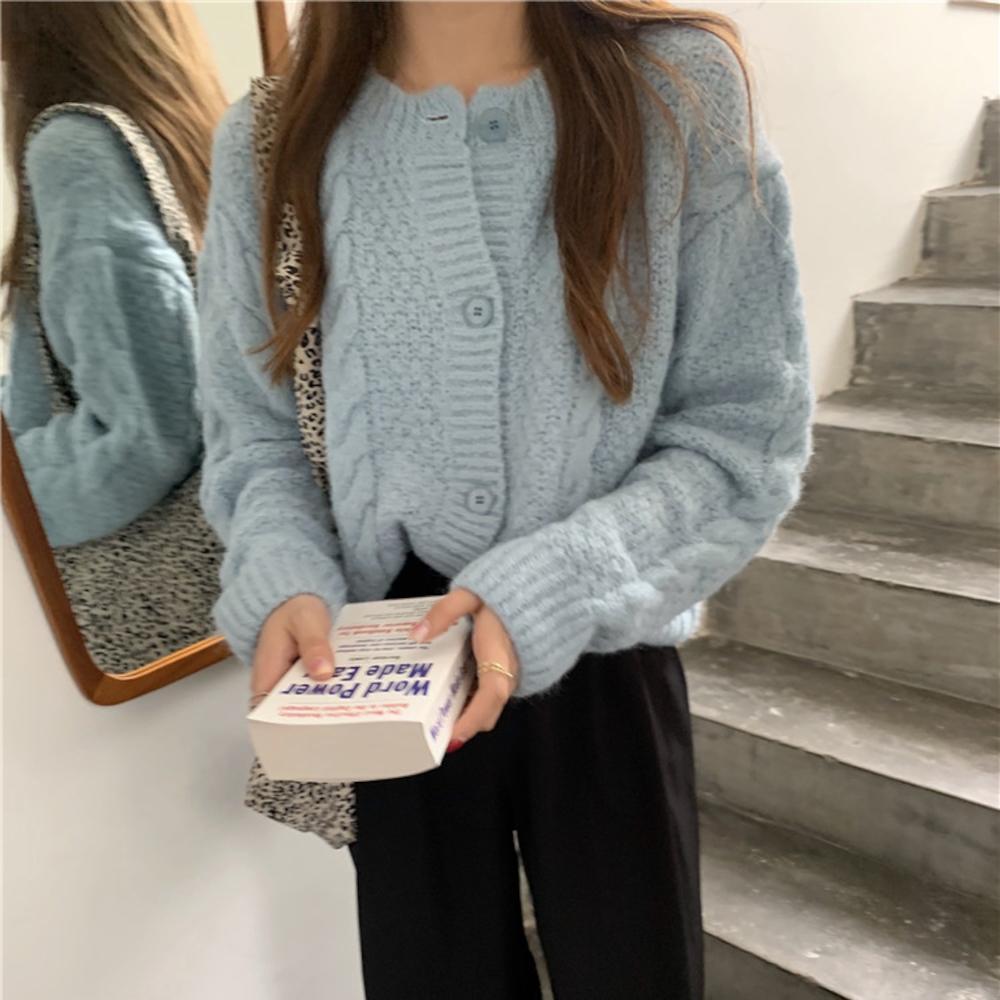 本をもった水色のセーターの女性